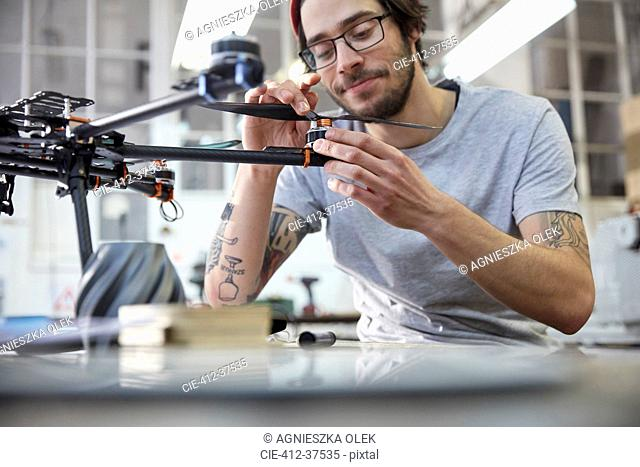 Male designer with tattoos assembling drone in workshop