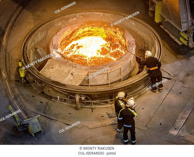 Steel workers inspecting molten steel in flask, high angle view