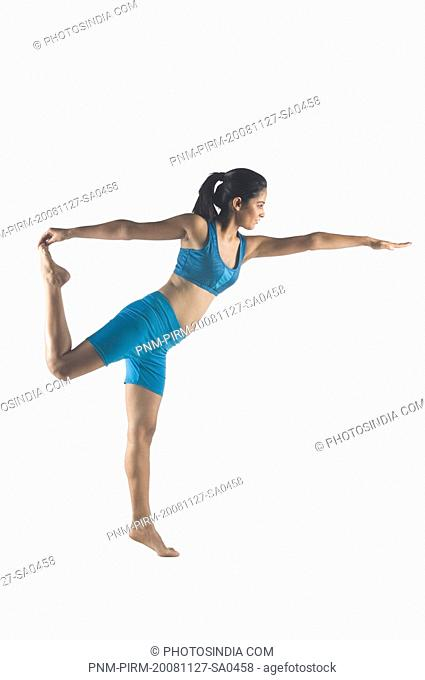 Side profile of a young woman stretching