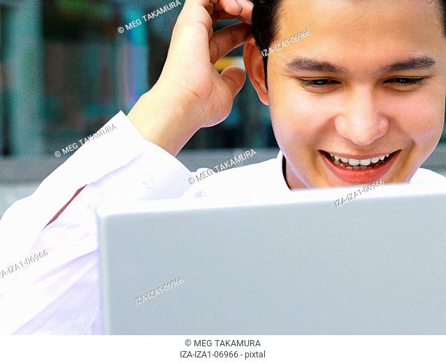 Close-up of a businessman using a laptop and smiling