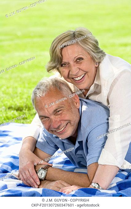 Active retirement laughing senior couple lying in grass