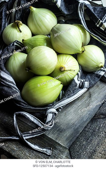 Onions in a black linen bag