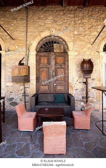 Upholstered seating furniture on stone floor in front of wooden door and quarrystone wall in Greece