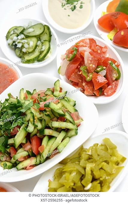 A table set with local salads such as eggplant, olives, Hummus, green salad and hot peppers usually served with pita as a mezze in middle eastern restaurants in...