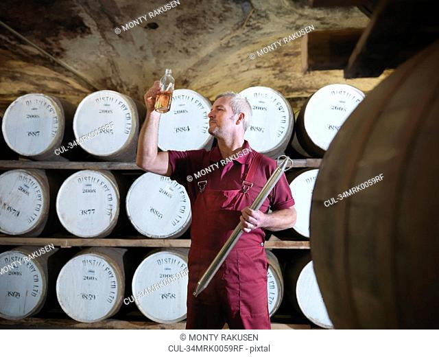 Workers checking whisky in distillery