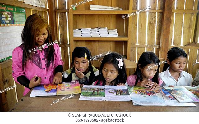 CAMBODIA. Projects of DPA in Stung Treng, supported by SCIAF. Katot village  Girls at the village literacy centre  With literacy teacher