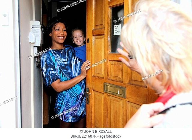Mother and toddler at doorway greeting visitor