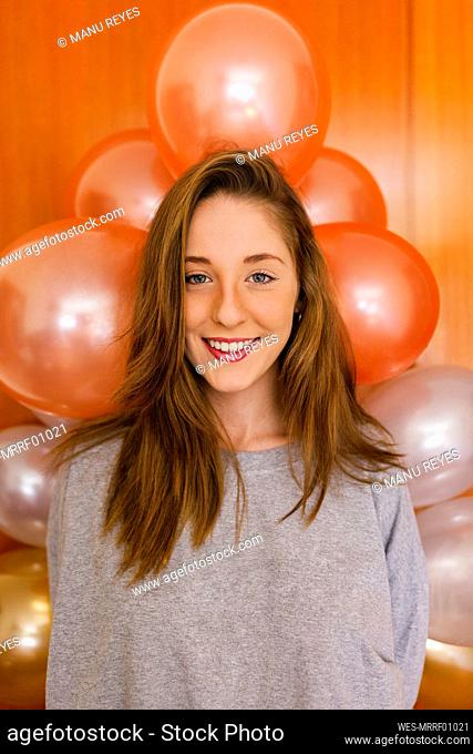 Woman standing by balloons decoration on wall at home