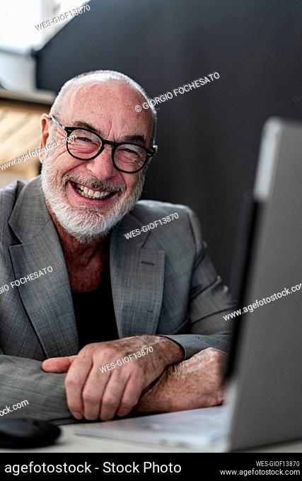 Cheerful senior businessman with laptop at studio