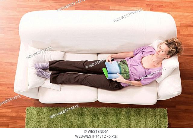 Germany, Cologne, Woman sleeping on sofa, elevated view
