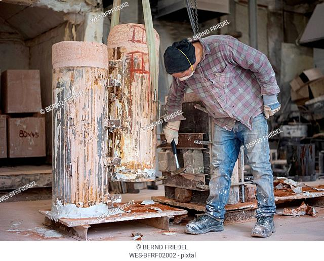 Art foundry, Foundry worker hammering on casting mould
