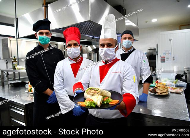 Mixed race team Portrait of group chefs standing together in the kitchen at restaurant wearing protective medical mask and gloves in coronavirus new normal...