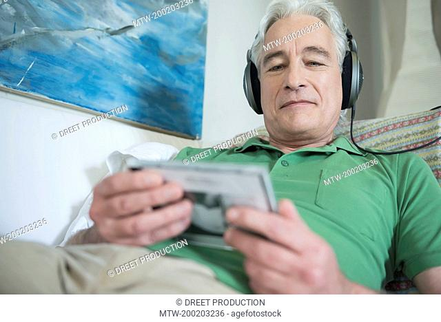 Mature man with headset sitting on couch and reading inlet of CD, smiling