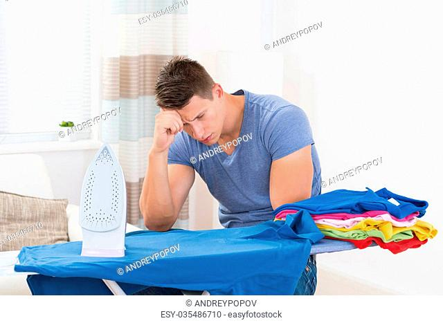 Upset Young Man With Electric Iron And Ironing Board