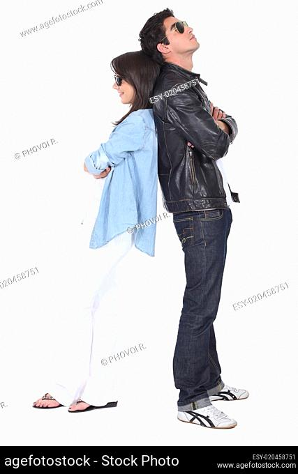 Young couple back to back in sunglasses and leather jacket