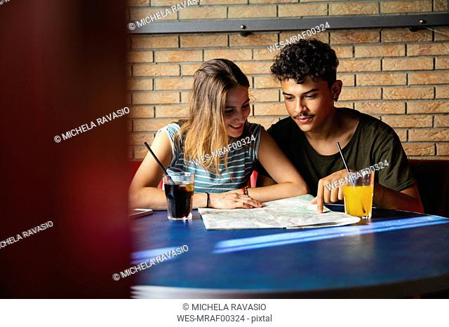 Smiling young couple sitting at table in a cafe with map