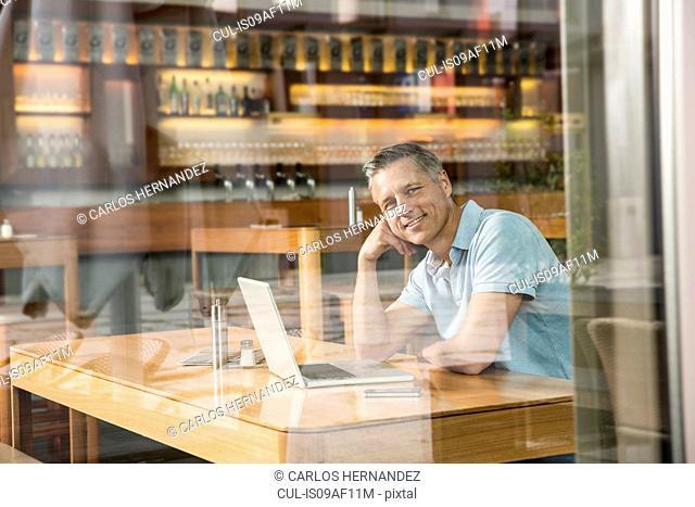 Businessman using laptop, view through window