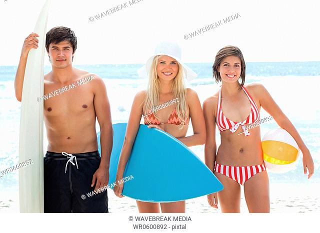 Man and two women looking forward with surfboards and smiling