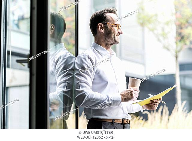 Laughing businessman with papers and coffee to go looking at distance