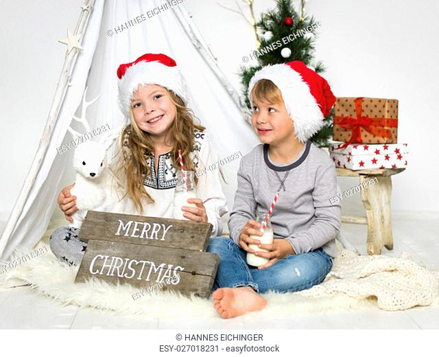 siblings drinking milk in the studio in a christmas scene