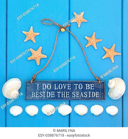 I do love to be beside the seaside sign, starfish, cockle and mother of pearl shells over wooden blue background
