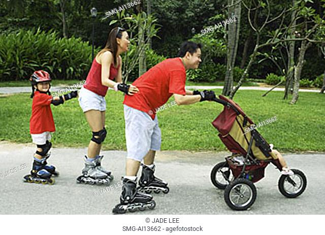 Family wearing roller blades, skating all in a row, father pushing stroller