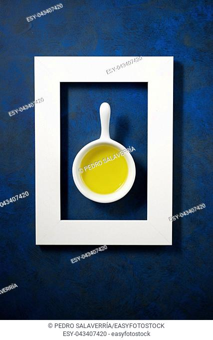 Olive oil in a small spoon on a blue table