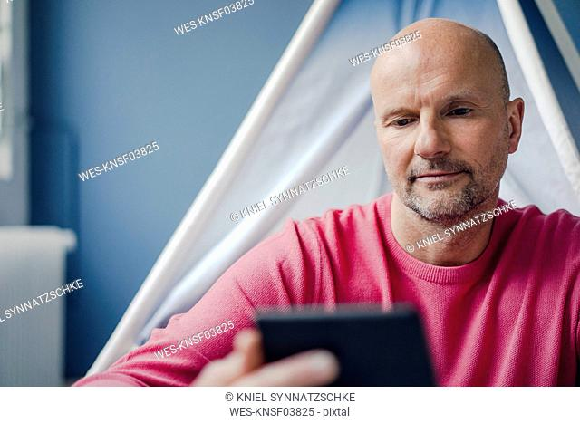Mature man sitting at teepee indoors looking at cell phone