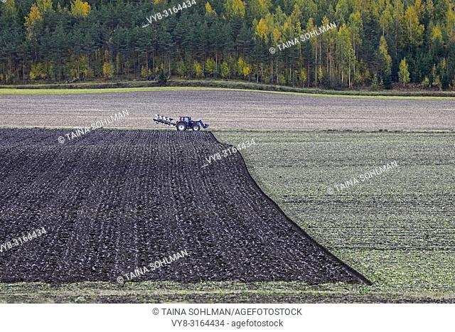 Agricultural landscape with tractor plowing a field in autumn
