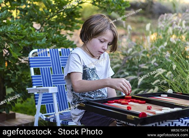 A young boy playing backgammon outdoors in a garden