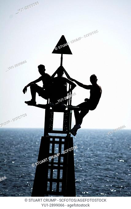 Silhouette of three youths balance on a harbour marker at the entrance to cartagena harbour in Murcia Spain