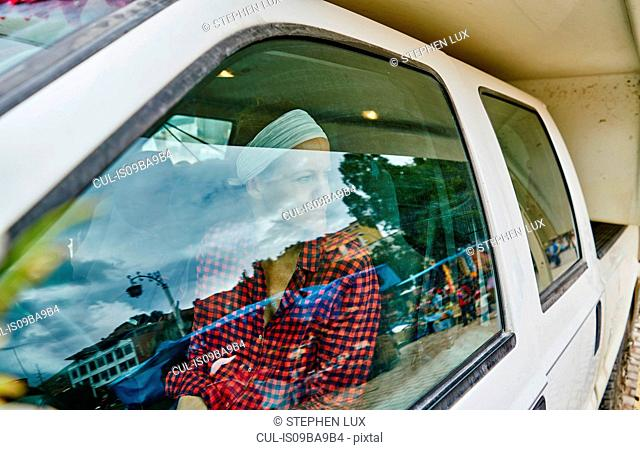 Woman inside recreational vehicle, looking out of window, Copacabana, Oruro, Bolivia, South America