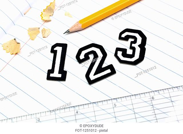 Varsity font sticker numbers 1, 2, 3 atop a lined paper notebook with ruler and pencil