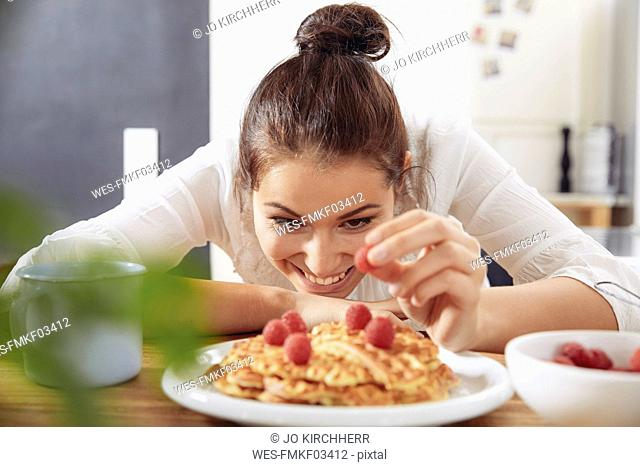 Portrait of happy young woman garnishing waffles in the kitchen
