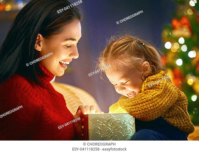 Merry Christmas and Happy Holiday! Loving family mother and child with magic gift box