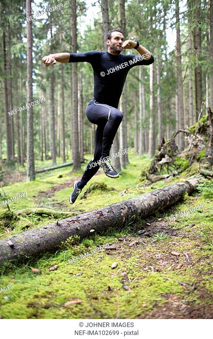 Mid adult man running through forest