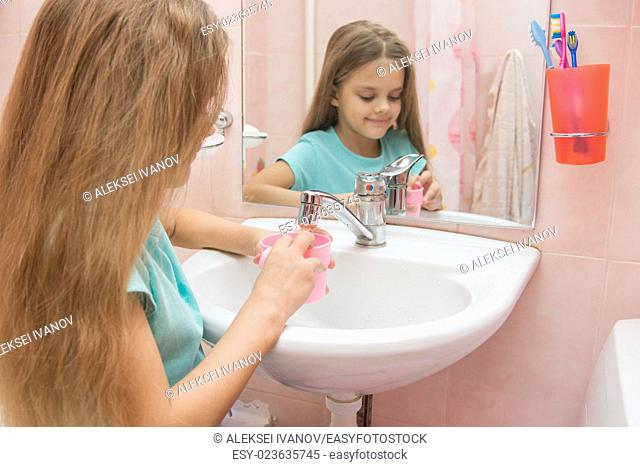 Six year old girl washes and brushes his teeth in the bathroom
