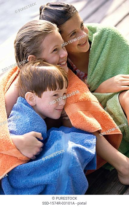 Two girls and a boy wrapped in towels sitting on a dock
