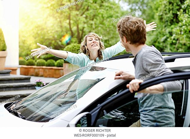 Happy woman with outstretched arms looking at man at car