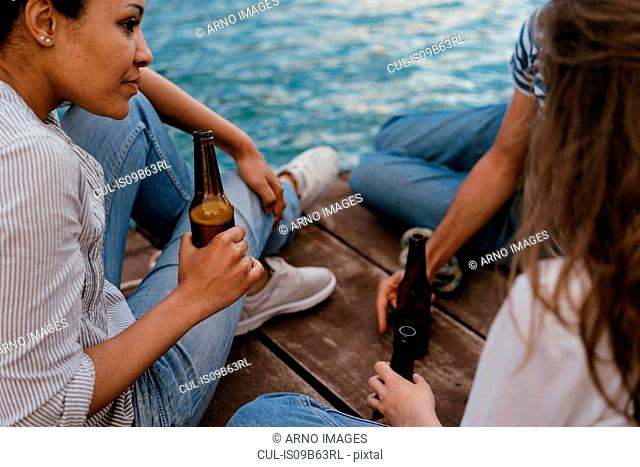 Three friends relaxing on pier, holding bottles of beer