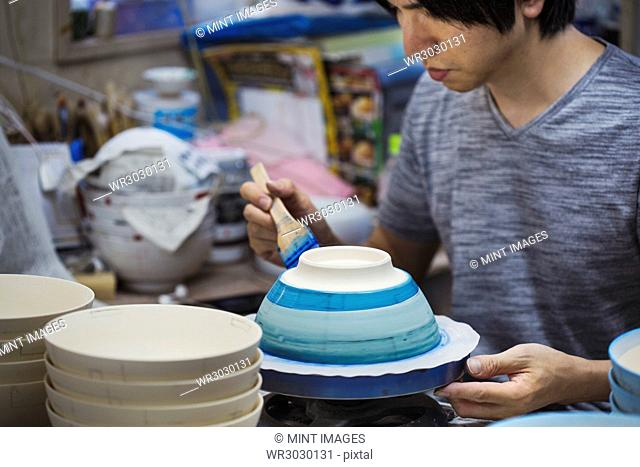 Close up of man working in a Japanese porcelain workshop, painting white bowls with blue glaze