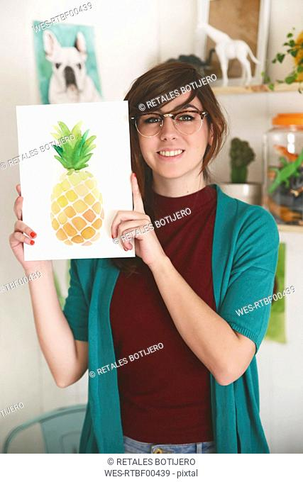Portrait of smiling artist showing her aquarelle of a pineapple