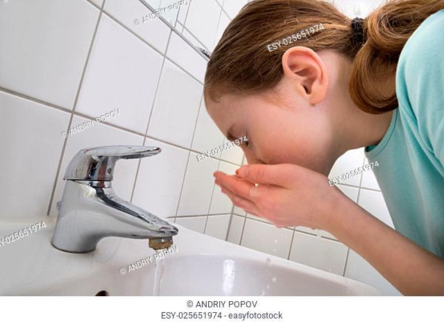 Little Girl Washing Mouth With Water In Bathroom