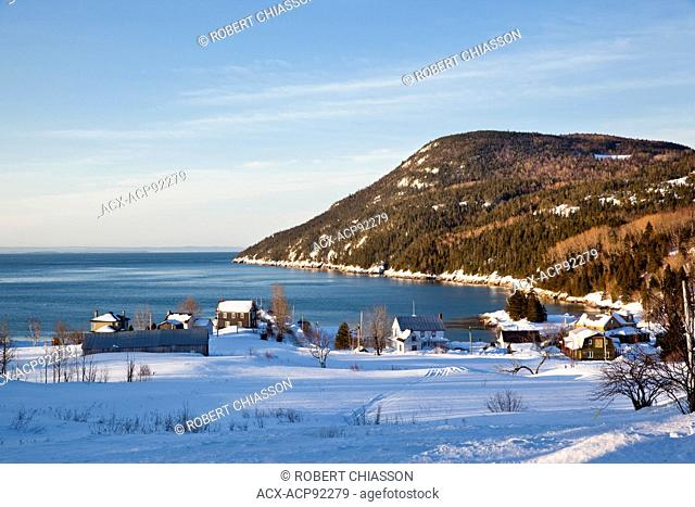 Winter scene of the coastal village of Port-au-Persil, Charlevoix, Quebec, Canada. In the background is the St. Lawrence River