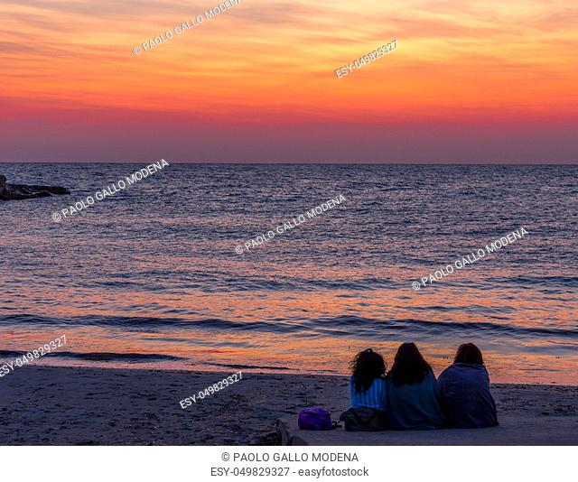 Three women waiting for the sunrise in front of the sea (Puglia region, South of Italy). Concept of frienship, travel and adventure