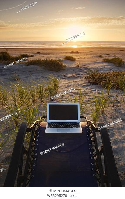 Laptop on deck chair overlooking sunset on beach