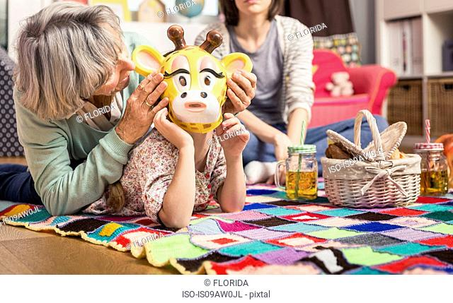 Girl wearing giraffe mask playing with grandmother on floor