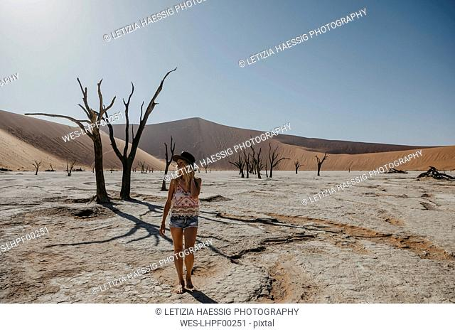Namibia, Namib desert, Namib-Naukluft National Park, Sossusvlei, woman walking in Deadvlei
