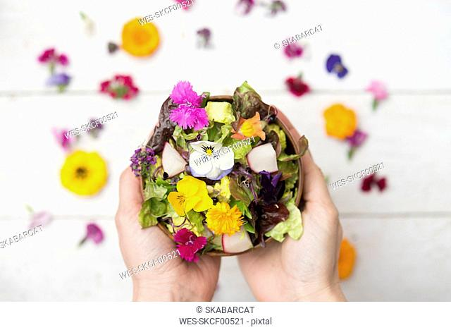 Woman's hands holding bowl of salad with edible flowers