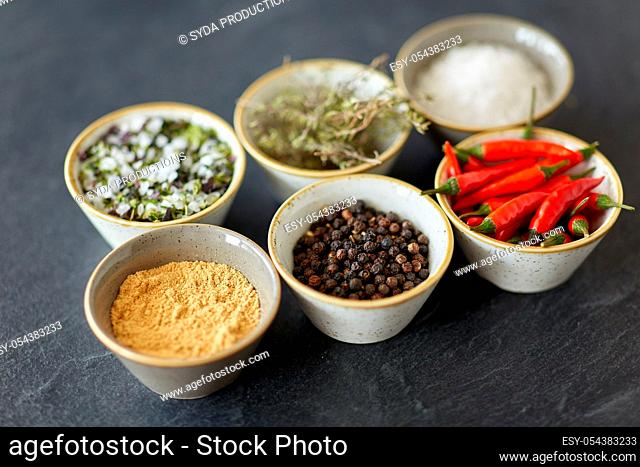 bowls with different spices on slate stone table